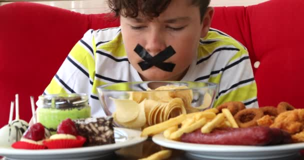 Mund eines kleinen Jungen mit Klebeband mit Fast-Food-Teller verschlossen 3
