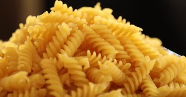Heap of rotating fusilli pasta on plate closeup