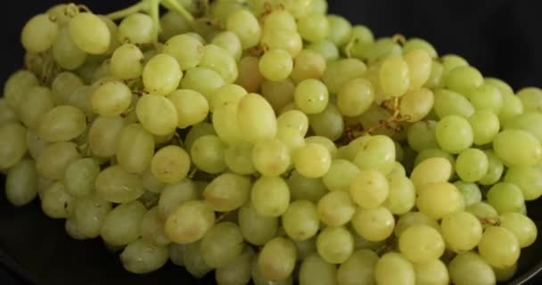 Bunch of white ripe grapes rotating on black background