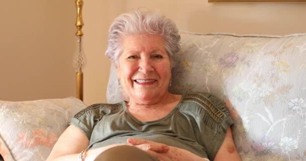 Porträt einer Seniorin, die zu Hause auf dem Sofa sitzt und in die Kamera lächelt