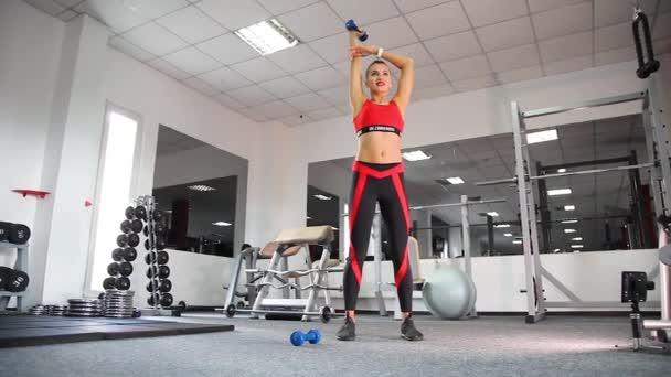 Malá štíhlá dívka opravuje postavu v tělocvičně. Mladá žena dělá fitness cvičení v tělocvičně. Bezbrendu: přeloženo z ukr znamená, že oděv nemá logo a nepatří do žádné značky nebo ochranné známky.
