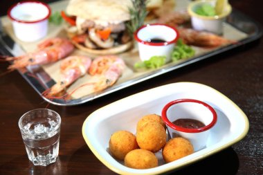 Fried balls of cheese. Cheese balls fried in breadcrumbs with sauce. Deep Fried Breaded Cheese. Burger and langoustines with sauce on a tray.