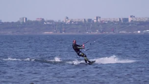 A kiteboarder of male jumps over the surface of the water of a large river. Splashes of water scatter in different directions. Sunny spring day