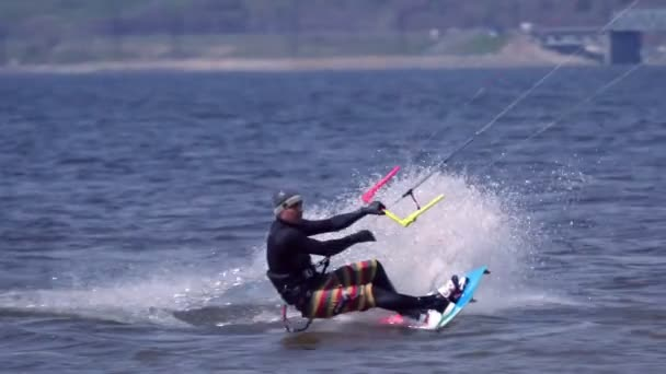 SLOW MOTION:A kiteboarder of male jumps over the surface of the water of a large river. Splashes of water scatter in different directions. Sunny spring day