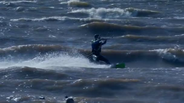 SLOW MOTION: Kiteboarder rides on the board on the waves. Summer sunny evening.