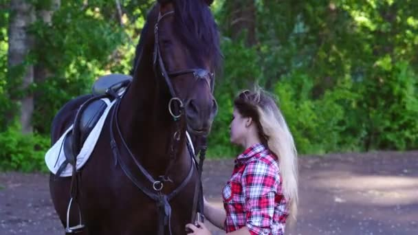 Young blonde woman in a plaid shirt takes a walk with his horse. Summer sunny evening.