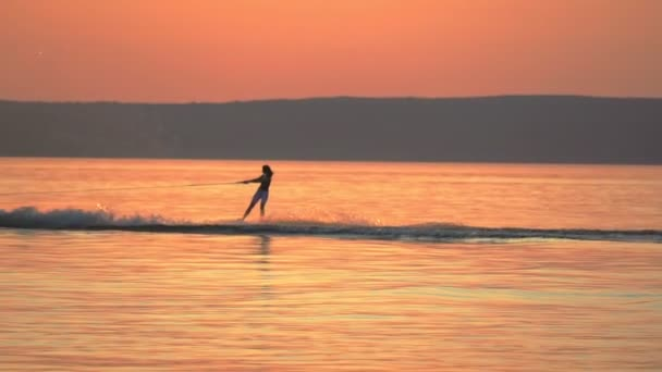 SLOW MOTION: A woman is engaged in wakesurfing. She rolls on a board over the smooth surface of the water of a large river. Summer sunset.