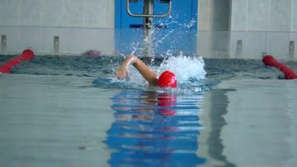 Slow Motion: Atletka plavání rychle v procházení stylu. Tryskající voda rozptýlená v různých směrech.