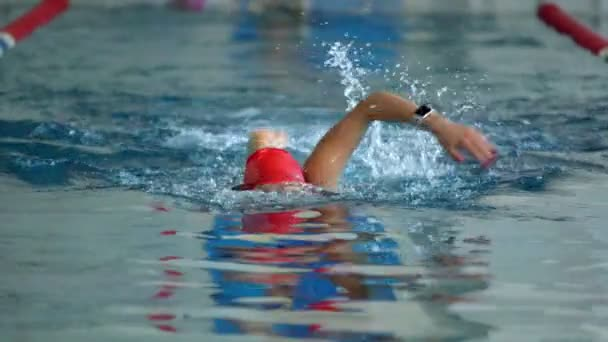 SLOW MOTION: Female athlete swimming fast in crawl style. Splashes of water scatter in different directions.