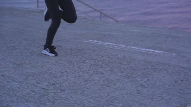 SLOW MOTION: Women's legs in black sweatpants and sneakers running along a concrete path along the riverbank in the morning before the dawn of the sun. Cold autumn morning.
