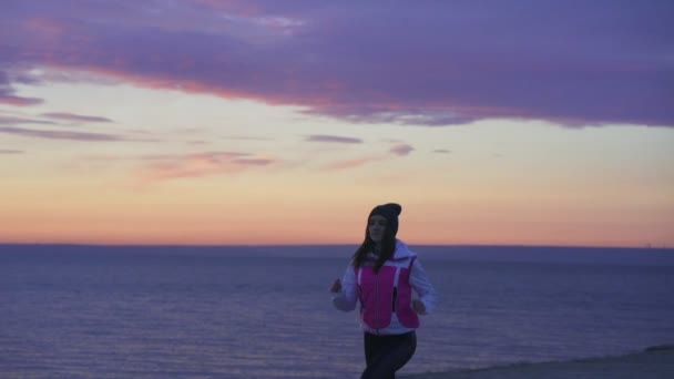 SLOW MOTION: A young girl in a sports hat and jacket makes a morning jog on the embankment in the morning before the dawn of the sun. A colder autumn morning.