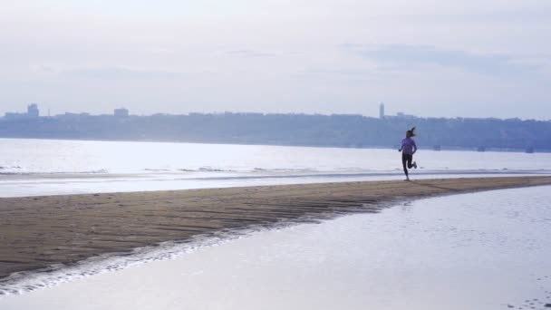 SLOW MOTION: Young slim brunette woman in sports uniform runs along the sandy shore on a summer morning. Morning sports run.