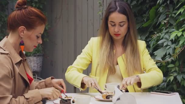 A középkorú vörös hajú nő egy barna kabátot és egy barna hajú fiatal nő egy sárga kabátot ülnek a nyári utcai kávézó és étkezési desszert. Közeli.
