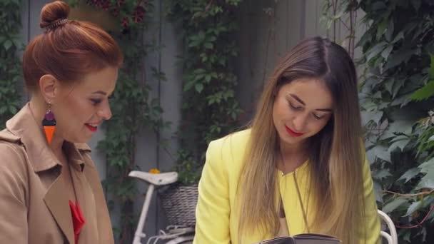 Egy középkorú vörös hajú nő egy barna kabátot és egy barna hajú fiatal nő egy sárga kabátot ülnek a nyári utcai kávézóban, csevegni és kiválasztja, hogy mit rendelni. Közeli.