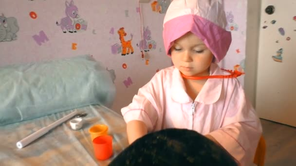 Das kleine Mädchen spielt beim Tierarzt. Der Hund liegt beim Arzt auf dem Tisch. Der Hund wird medizinisch versorgt.