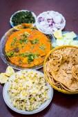 Nahaufnahme von dal makhani, einem indischen Gericht zum Mittagessen mit Gurkenscheiben, Zwiebel- und Hari-Chutney mit roti und weißem khichdi