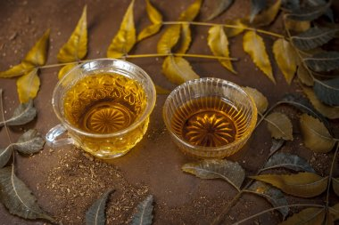 Neem tea with leaves on a wooden surface