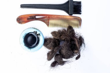 Damaged female hair with brushes and dye on white background