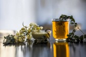 Bunch of flowers of drumstick on wooden surface along with its extracted water or tincture in a glass.