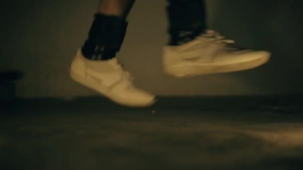 Nohy nosí černé barvy kotníků závaží a dělá různé skákání a běh cvičení.