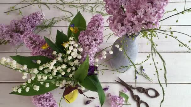 create beautiful flower arrangement, delicate lilac, white Lily of the valley poor flower shaped boot, green leaves, various decoration, pastel colors, on a wooden table vintage scissors, video shooting with approximation