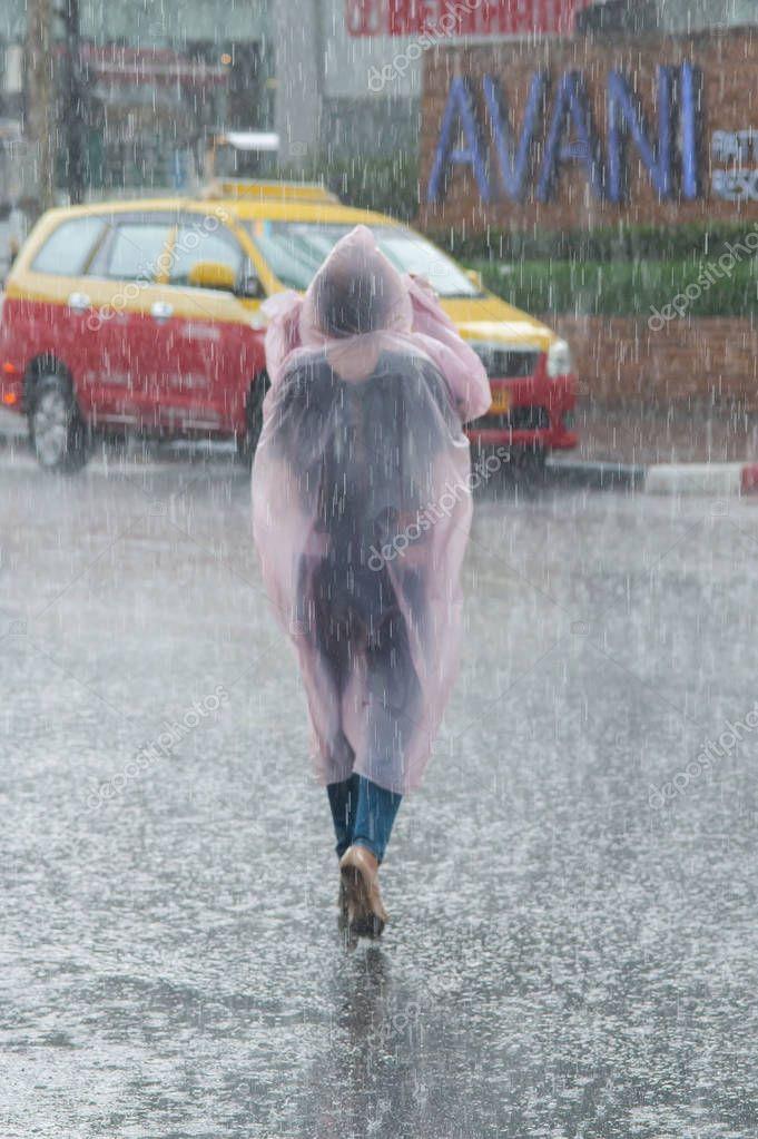 PATTAYA THAILAND - CIRCA MAY 2018.  Undefined girl in a raincoat crossing the street during heavy tropical storm rain. Monsoon season. Day editorial shot
