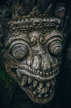 Closeup portrait of stone traditional sculpture art form incorporated into temples, which demonstrate the influences of Hindu Buddhist culture. Bali, Indonesia