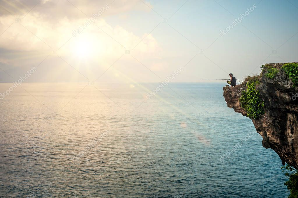 BALI, INDONESIA - 30. APRIL 2018. Man fishing on edge of cliff on the Indian coast. Day editorial shot