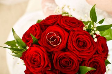 wedding bouquet of red roses and rings