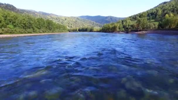 Moving over a mountain river with clear water. Aerial photography. A beautiful mountain valley with a river in the sunlight. Primordial nature. Mountain Altai.