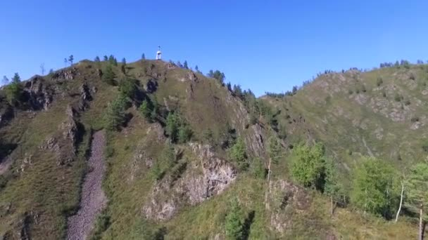 Aerial survey of the Katun River valley with a chapel on the mountain peaks. Cross over the valley of a mountain river.