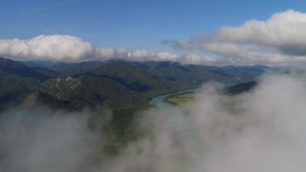 Aerial photography in the Altai Mountains. Flying in the clouds over the picturesque landscape of the Katun River valley with the mountains going into the distance.