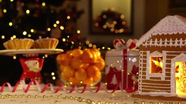 Szilveszteri karácsonyi ünnep asztalra. Karácsonyi hangulat. Mézeskalács házikó, ünnepi fények.