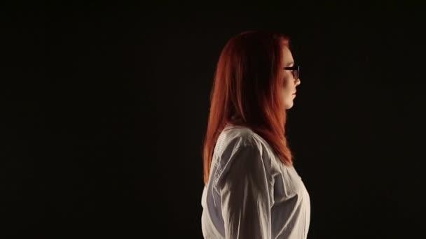 krásná dívka s červenými vlasy v bílé košili pózuje na černém pozadí před kamerou. model inzeruje brýle, čočky nebo obnova vidění