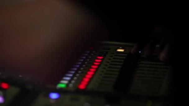 Remote Recordists Nahaufnahme. Hand passt Soundeffekte an. elektrische Maschine auf dem Tisch für die Arbeit von Sounddesigner oder Club-DJ auf einer Party in einem Nachtclub. Beschäftigung für modernen Lebensstil, Objekte zum Zuhören im Hintergrund. Musikanlage zur Abstimmung der Bühnenklo