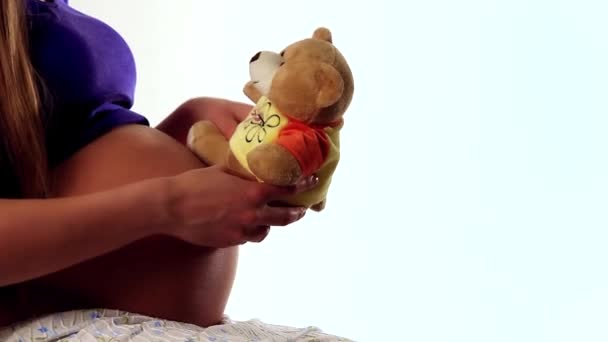 Woman pregnant with kid holding teddybear close to belly playing.