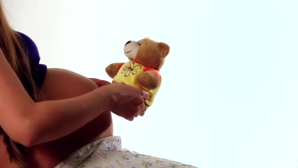 the concept of healthy living, motherhood, playing with a baby - a Woman is pregnant while holding a Teddy bear close to her belly.