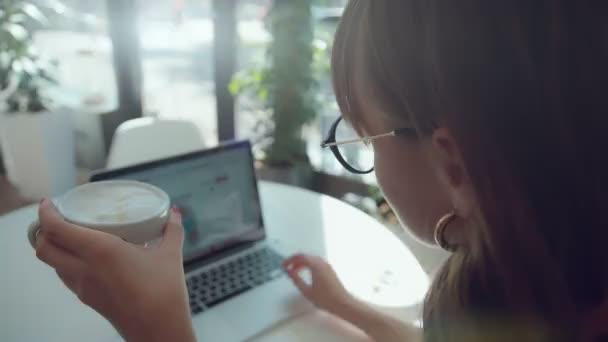 Elegantní a stylová žena užívat kávu a laptop na světlém café