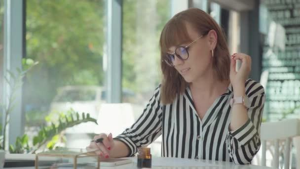 Elegantní mladá žena se zabývá kaligrafie. Inkoust a pero