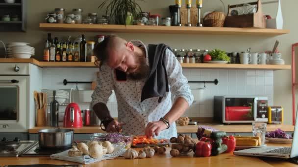 Vidám szakállas férfi, főzés a konyhában, és beszél a telefonon