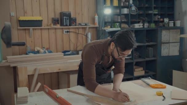 Muž v truhlářské dílně se naklonil přes stůl s nástroji, udělala poznámky tužkou na dřevěné prázdné. Master navrhuje nábytek, dělá značky na dřevěný bar. Tesař s brýlemi a vousy