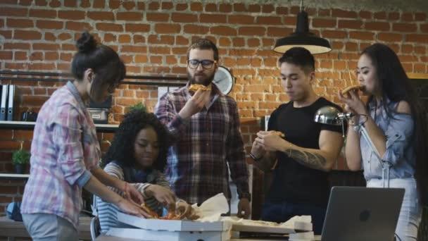 Kollégák hivatalban pizzát eszik együtt