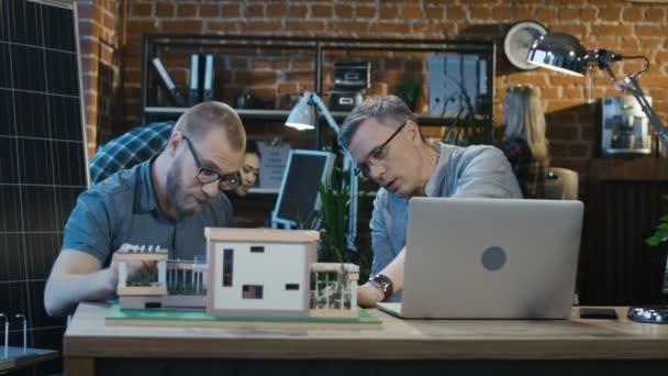 Menschen arbeiten an Miniatur eines modernen Hauses