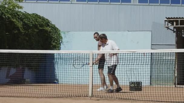 Tenisový trenér pracuje s mužem na kurtu