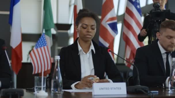afrikanisch-amerikanische Abgeordnete der Vereinigten Staaten hält Rede über Bitcoin, während sie bei einem internationalen Treffen am Tisch sitzt