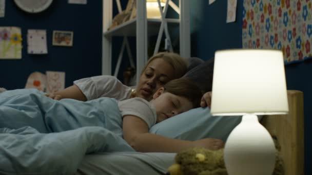 Woman putting girl to sleep