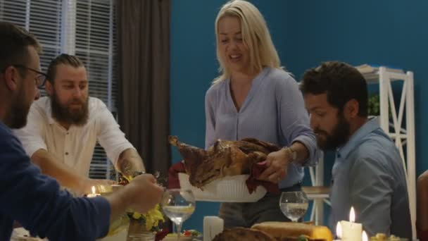 Woman serving holiday turkey on dinner with friends
