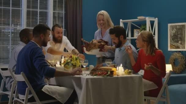 Vidám nő hozza és szolgáló hatalmas sült Törökország asztalon, miután a barátokkal a Hálaadás ünnepe