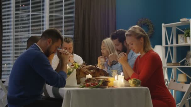 Group of friends praying on Thanksgiving day celebration