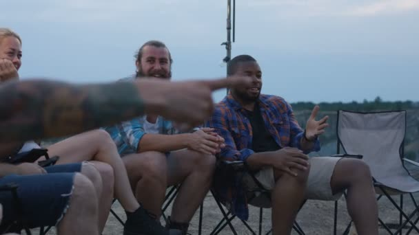 Laughing diverse friends playing charades in camp